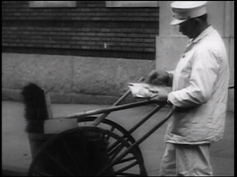 B/W 1938 streetsweeper standing by cart on street playing with puzzle / newsreel