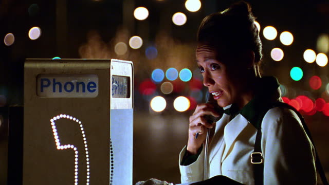 Stressed Black woman talking on pay phone on city street at night