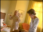 Stressed woman trying to talk on phone while twin blonde girls are screaming + jumping on bed