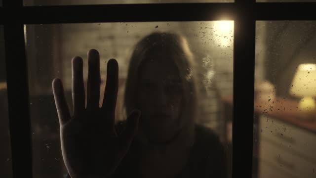 Stressade kvinnor håller hand i fönster
