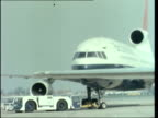 London Heathrow EXT MS as Trident plane back in tow MS side passengers RL and up plane steps MS British Airways Tristar in tow RL MS steps pushed to...