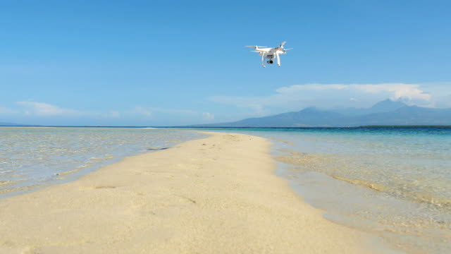 Strip of white sand beach and drone flying overhead, tropics