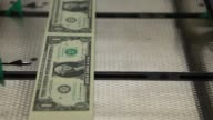 Stripes of one dollar notes pass through a KBANotaSys SA large examining packaging machine while being cut into individual bills at the US Bureau of...