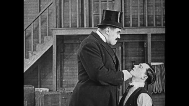 A strongman hooks Buster Keaton around the neck with a cane and bullies him
