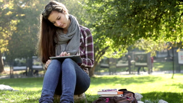 Student girl studying on digital tablet in the campus.