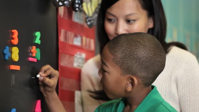CU PAN TU TD Student learning addition at blackboard with teacher's help / Richmond, Virginia, United States