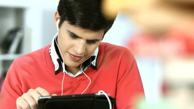 HD: Studente Utilizzando la tavoletta digitale In biblioteca