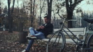 Student using his smartphone while sitting in the park