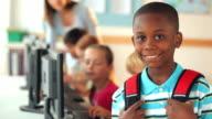 Student with backpack smiling in classroom