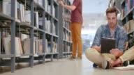 DS studente con cuffie navigazione libri su compressa in biblioteca