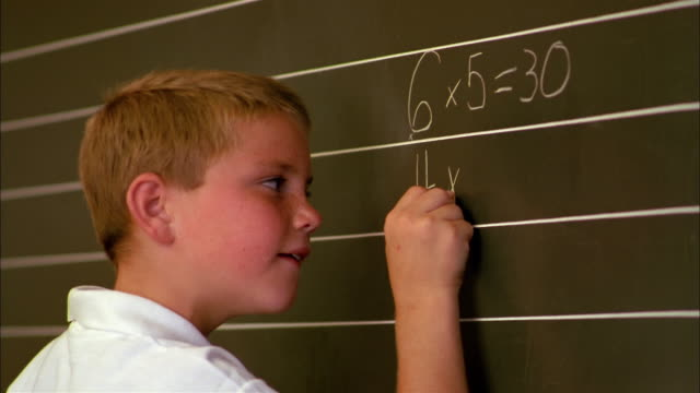A student writes multiplication tables on a chalkboard.