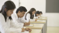 Eleverna besvarar ett test och manlig student tänkande svaret