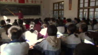MS PAN Students at desks in crowded classroom listening to teacher pointing at chalk board, Weishan, Yunnan, China