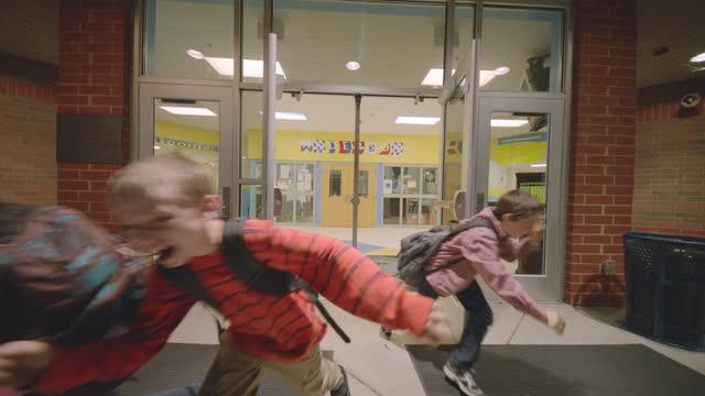 Students bust through school doors (slow motion)