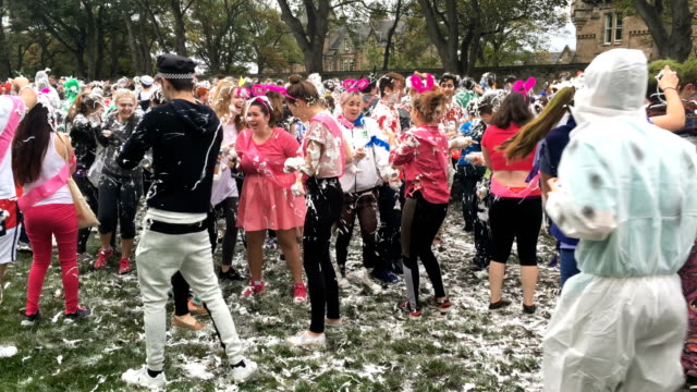 Students from St Andrews University indulge in a tradition of covering themselves with foam to honour the 'academic family' on the lower college lawn...