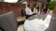 Students get GCSE results amid biggest shake up in years Greater Manchester EXT Nikita Murray setups sitting with her parents in garden looking at...