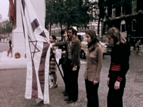 Students holding the Israeli flag bow their heads at the Cenotaph London in memory of the 11 Israeli athletes murdered by the Black September...