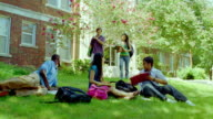 MS, students joining in and sitting with colleagues on grass on campus, San Antonio, Texas, USA