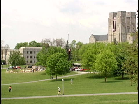 Students on Virginia Tech campus man sitting under tree reading book / American flag at halfmast / memorial in front of Burruss Hall for massacre...