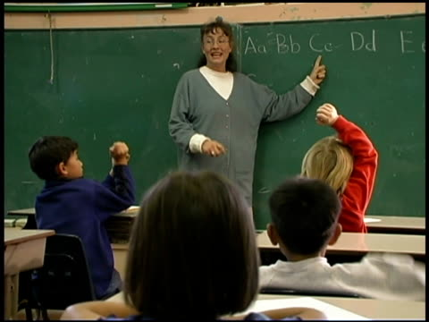 Students raising hands with teacher in classroom