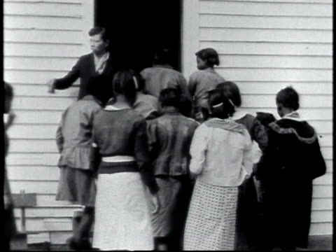 1940 WS students reentering school house as teacher is standing by door ringing bell / Calhoun, Alabama, United States