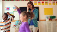 Students running around frustrated teacher in classroom