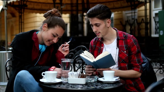 Students studying in cafe, smoking and smiling