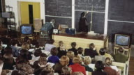 1965 MONTAGE Students taking notes at a lecture while a teacher is standing at a blackboard and another is demonstrating / Brighton, England, United Kingdom