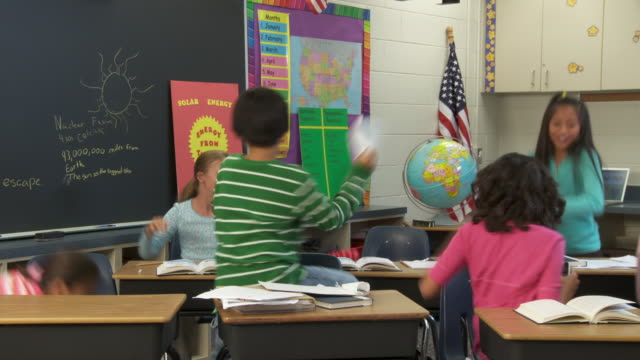 MS, Students (8-13) throwing paper at each other in classroom, Richmond, Virginia, USA