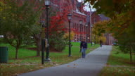 Students walk along campus pathway with trees in autumn leaf, University of Vermont Available in HD.