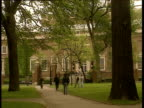 Students walk through tree-lined path with Harvard University building in background
