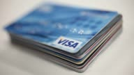 Studio BROLL of various kinds of Visa credit cards and debit cards laid out on a black background Studio BROLL of various kinds of Visa credit cards...