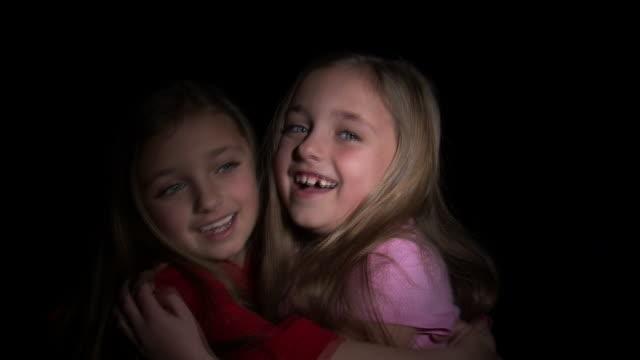 CU Studio portrait of twin sisters (8-9) hugging / Orem, Utah, USA