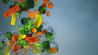 SLO MO CU Studio shot of assorted vegetables falling in water