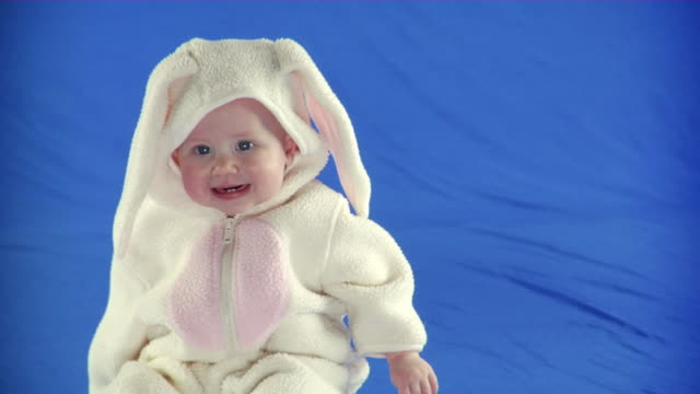 MS PAN Studio shot of baby girl (6-11 months) in bunny costume on blue screen