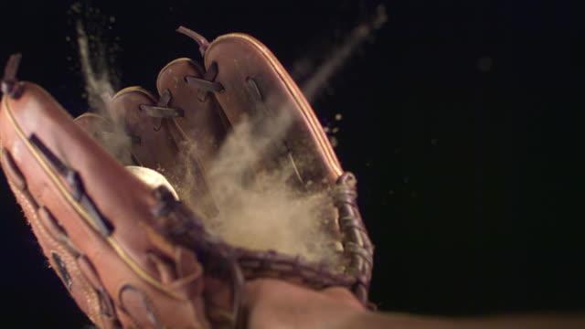 SLO MO, CU, Studio shot of baseball falling into glove