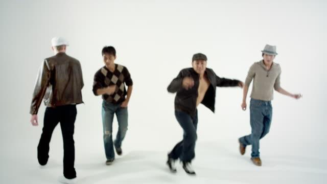 MS Studio shot of boy band dancing and singing