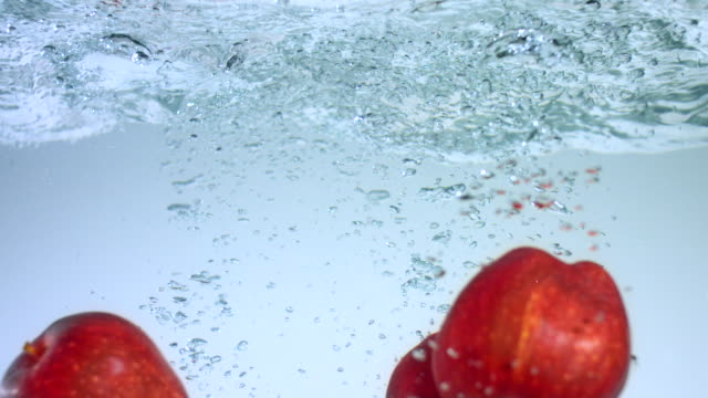 SLO MO CU Studio shot of five apples moving up in water