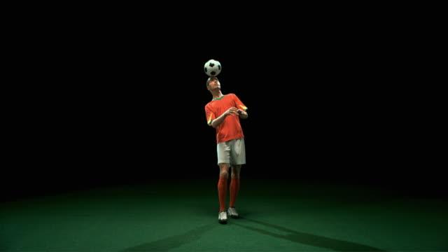 SLO MO WS Studio shot of football player training