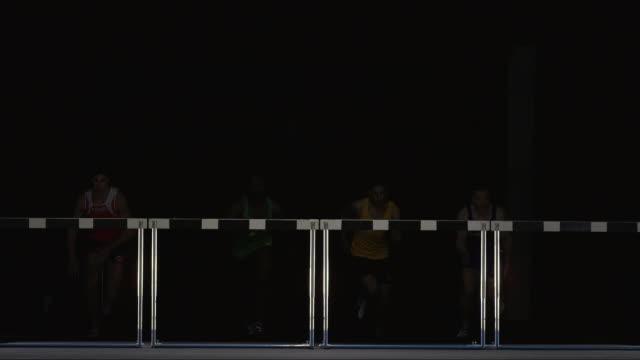 SLO MO WS Studio shot of four male athletes jumping hurdles