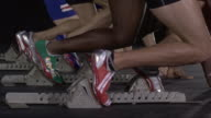 SLO MO CU Studio shot of four male runners at starting blocks, low section