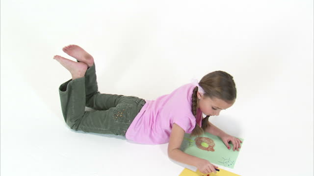 MS Studio shot of girl (8-9) drawing / Orem, Utah, USA