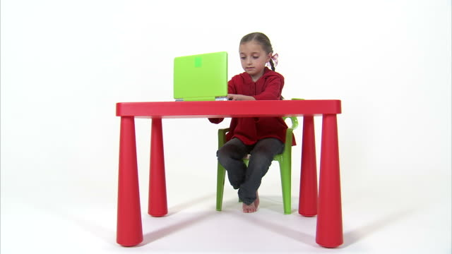 WS Studio shot of girl (8-9) using laptop at red table / Orem, Utah, USA