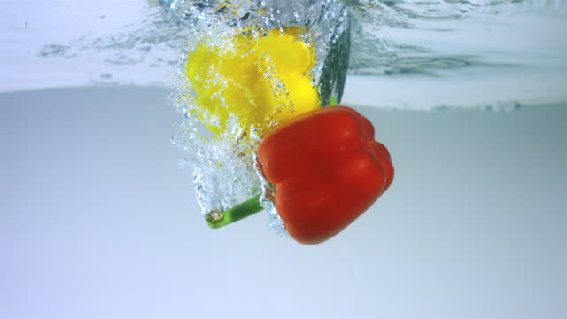 SLO MO CU Studio shot of green, yellow and red bell peppers falling into water