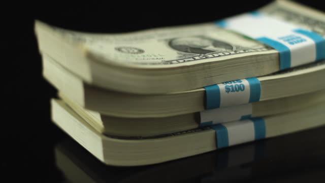 CU SLO MO Studio shot of growing stack of One Dollar Bills