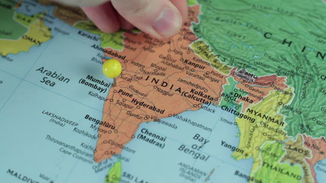 CU Studio shot of hand placing pin into map of Asia