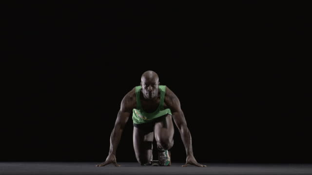 SLO MO WS Studio shot of male runner at starting blocks