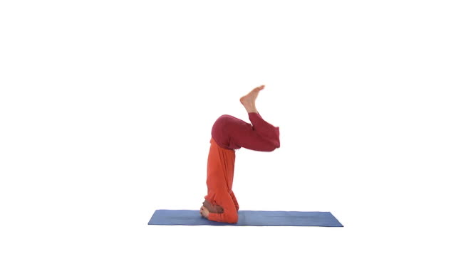 WS Studio shot of man doing scorpion pose on exercise mat