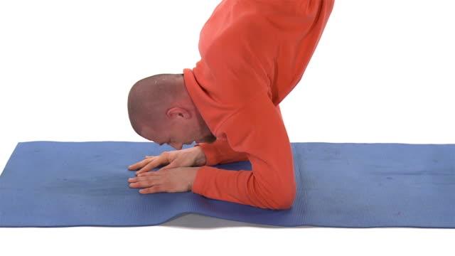 CU ZO WS Studio shot of man doing scorpion pose on exercise mat