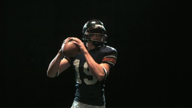 SLO MO MS Studio shot of quarterback throwing ball